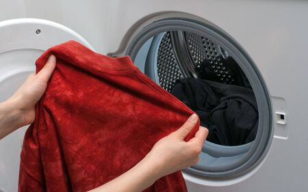 washing hand: Hands placing the clothes in the drum of washing machine