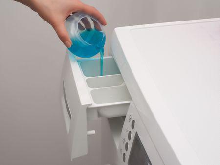 detersivi: Aggiunta di detergente al distributore della lavatrice Archivio Fotografico