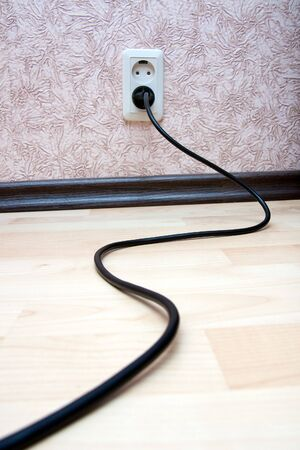 electric socket: Black cord on the laminated floor Stock Photo