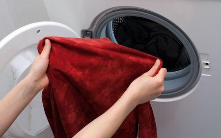 Hands placing the clothes in the drum of washing machine photo