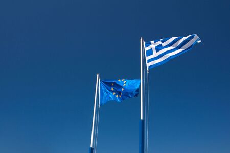 EU and Greece flags against clear blue sky photo