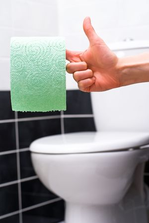 Human hand holding green toilet paper on the background of toilet bowl photo