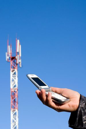 communications technology: Cellular telephone in a hand against the GSM base station