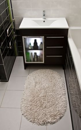 Bathroom carpet and cabinet with toiletries in modern interior  photo