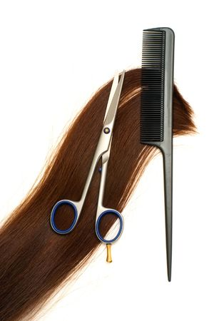 Scissors, hairbrush and lock of hair isolated on white background photo