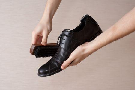 Hand polishing black mens boot witn brush photo