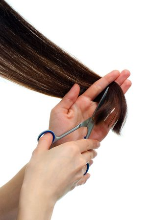 haircutting: Hand with professional scissors cutting brown hair  Stock Photo