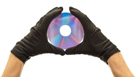 Hands in black gloves holding cd or dvd disk isolated on white background photo