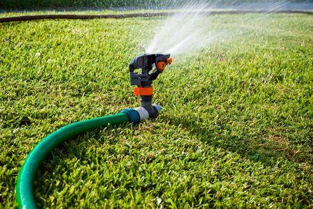 lawn sprinkler: Lawn sprinkler spraying water on the grass Stock Photo