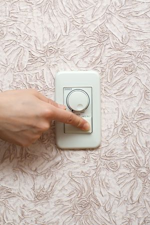dimmer: Womens hand switches off light in the room