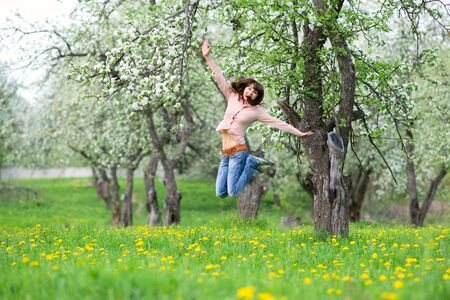 Cheerful young woman jumping in the garden photo