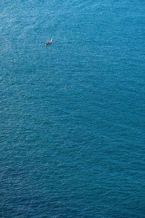 surface view: Single boat in the blue tranquil sea