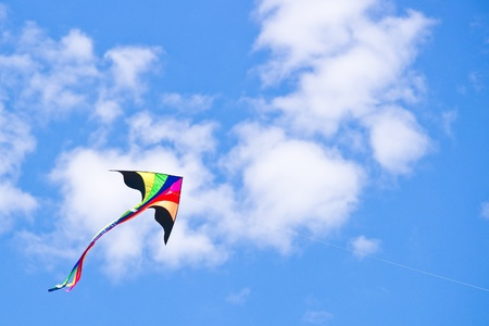 kite flying: Multicolored kite flying in blue cloudy sky Stock Photo