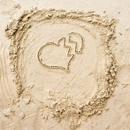 unrequited love: The drawing of breaken heart on the sand Stock Photo