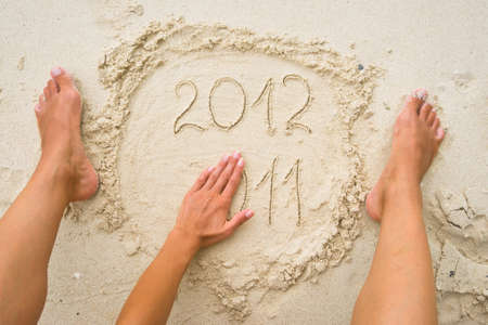 expiring: Female hand erasing numbers 2011 on the sand