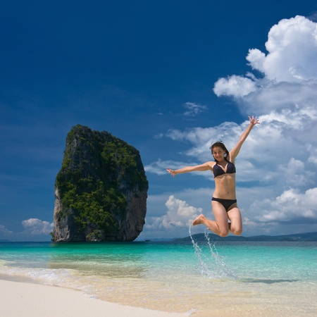Young cheerful woman is jumping on the beach photo