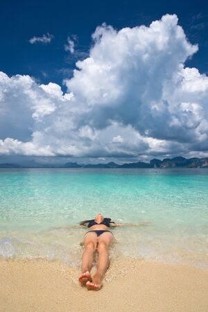 Woman lying in the turquoise sea and taking sunbath photo