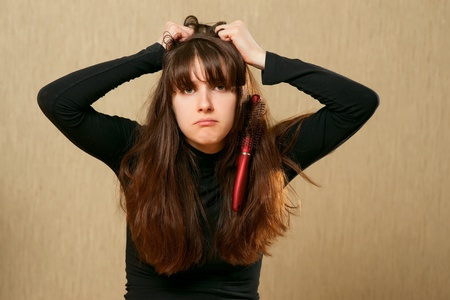 bad hair day: Frustrated young woman having a bad hair day with brush stucks in her hair