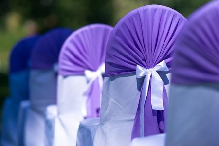 c�r�monie mariage: Des chaises de mariage avec des couvertures de pourpre et des rubans blancs