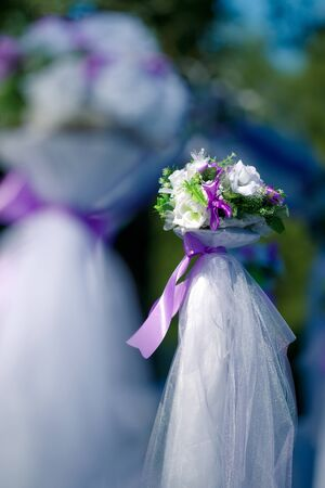 Wedding bunch of flowers decorated with purple ribbons and white organza photo