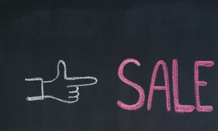 Hand pointing to the word Sale, written on a blackboard photo