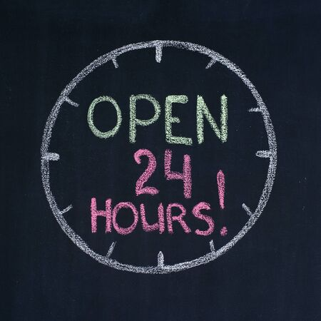 The dial with text Open 24 hours, drawn on a blackboard photo
