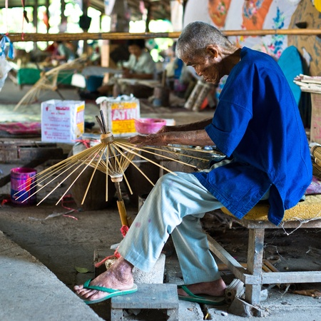 Bo Sang village, Chiang Mai province, Thailand - 9 January, 2012: Thai craftsman is making wooden frame of traditional asian umbrella in Bo Sang handicrafts village, Chiang Mai province, Thailand