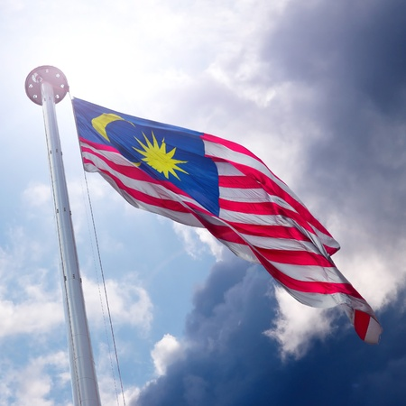 Waving flag of Malaysia on the cloudy sky background