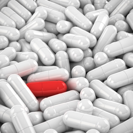 One red capsule in the heap of white capsules photo