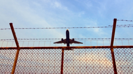 flight mode: Airplane is flying up over a metal fence Stock Photo
