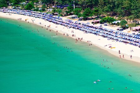 Crowd of tourists on the sandy beach of Phuket island, Thailand photo