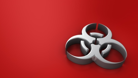Metal biohazard symbol on red background with copyspace photo