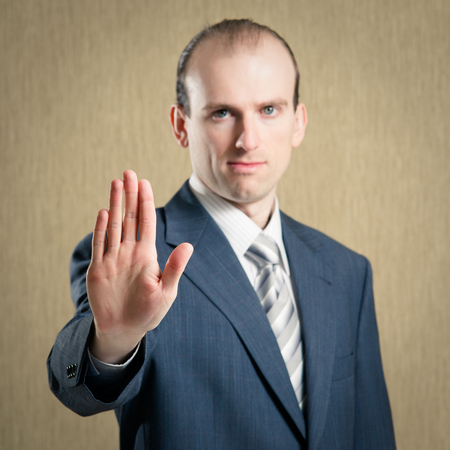 Businessman making stop gesture. Focus on the palm photo