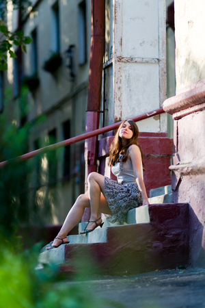 Young woman sitting on the steps of porch photo