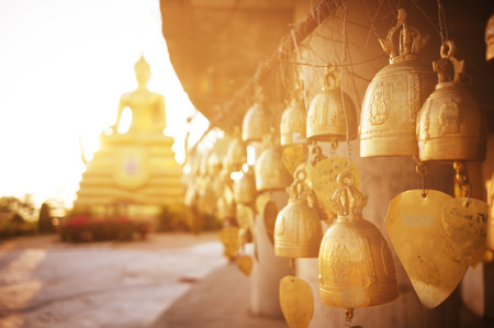 Buddhist bells with wishes hanging in the temple near the sitting Buddha
