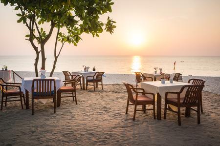 Empty restaurant on the sand beach in sunset Stockfoto