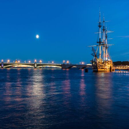 Water area of Neva river with illuminated bridge in white night in Saint Petersburg, Russia