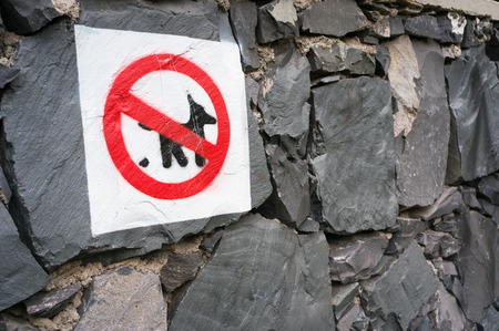 caution sign: Pets poop ban sign painted on the stone wall of the park