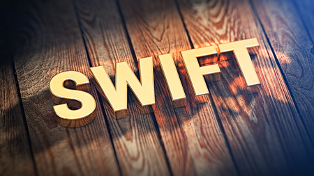 interbank: Bank wire transfers system. The word SWIFT is lined with gold letters on wooden planks. 3D illustration picture