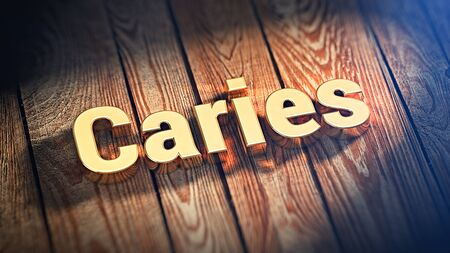 jpeg: The word Caries is lined with gold letters on wooden planks. 3D illustration jpeg