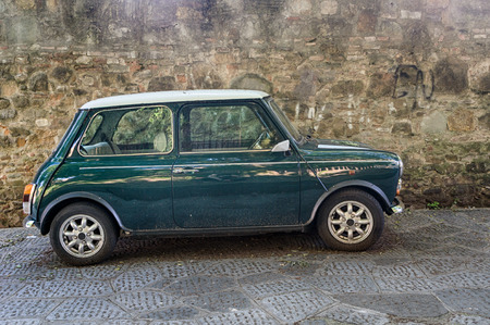 cooper: Florence, Italy - April 29, 2016. Mini Cooper MKVI car parked next to old stone wall