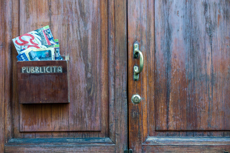 mail slot: Florence, Italy - May 12, 2016: Mailbox for advertising on the wooden door with text in italian Pubblicita Editorial