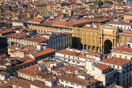 overpopulated: Top view on the red tiled roofs of Florence city and the arch of Piazza della Repubblica, Italy