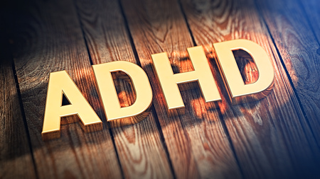 hyperactivity: The acronym ADHD is lined with gold letters on wooden planks. 3D illustration image