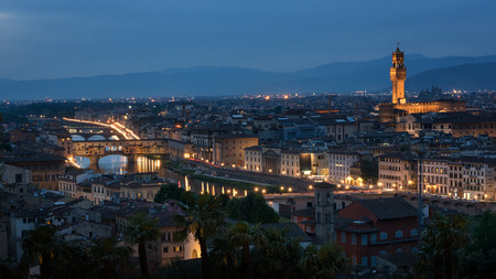 michelangelo: Cityscape of Florence in night illumination of famous landmarks - Ponte Vecchio and Palazzo Vecchio on the opposite riverside. View from piazzale Michelangelo.