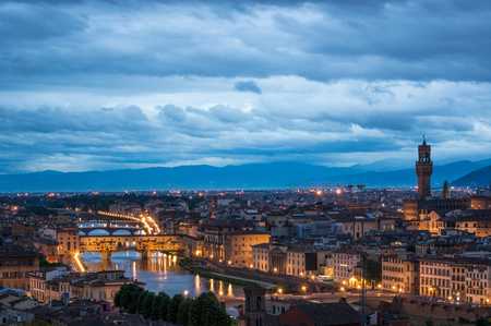Cityscape of night Florence with famous landmarks - Ponte Vecchio and Palazzo Vecchio. View from piazzale Michelangelo on the opposite riverside, Italy.