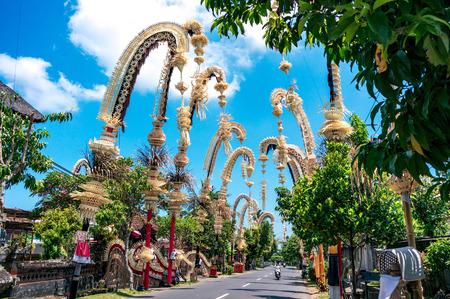 Les penjors balinais traditionnels le long de la rue de Bali, en Indonésie. De grands bâtons de bambou décorés sont placés en l'honneur des dieux hindous lors de fêtes religieuses comme Galungal, Kuningan.