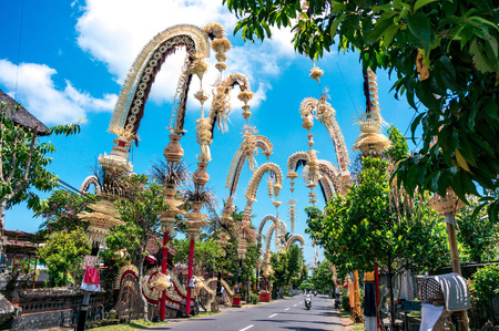 Traditional balinese penjors along the street of Bali, Indonesia. Tall bamboo poles with decoration are set in honour of hindu gods on religious festivals like Galungal, Kuningan. Banco de Imagens