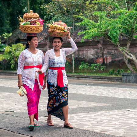 UBUD, INDONESIA - OCTOBER 15, 2016: Balinese women are carrying the gifts for the gods on the heads. The religious ceremony during the festival in Tirta Empul temple on Bali