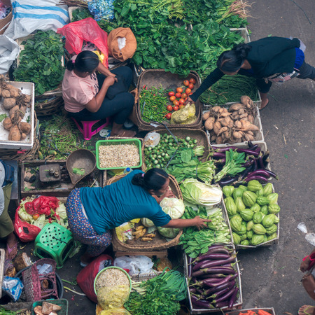 BALI, INDONESIA - NOVEMBER 3, 2016: Balinese women selling the vegetables on the main market of Ubud, top view